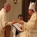 The newly ordained deacon receives the Book of the Gospels.